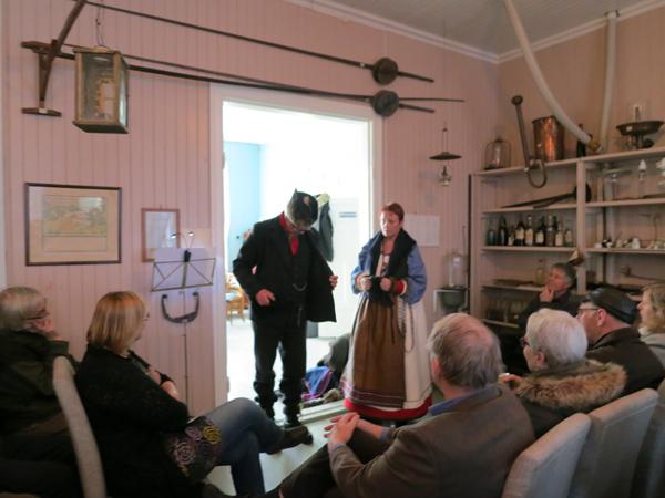 Mari Bryhni forteller om lasskjørernes bekledning. Helge viser fram hva de brukte - ull, ull, ull og skinn. Foto: Karine Bogsti