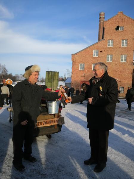 Stanges ordfører Nils Røhne (t.h.) får flaske fra lasskjørerne som han sendte videre til Røros ordfører. Vi tar den med på lasset, og lover den skal komme trygt fram! Foto: Karine Bogsti